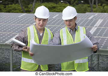 Two Asian solar-panel engineer's at work.