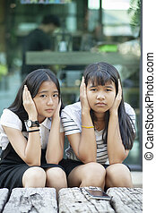 two asian teenager using hand close her ear for not...