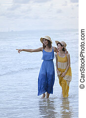 two asian woman relaxing vacation time on sea beach