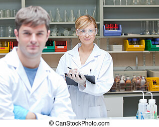 Two assertive scientists looking at the camera standing