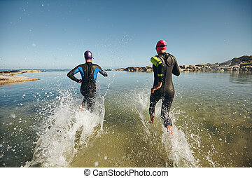 Two athletes competing in a triathlon - Two athletic...