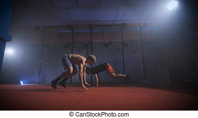 Two athletes doing difficult crossfit exercise at the same...