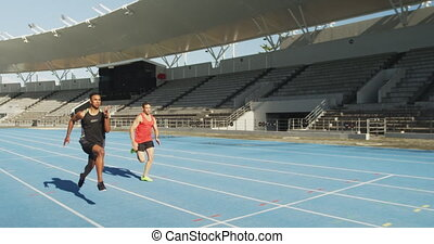 Two athletes running in stadium - Side view of a Caucasian ...