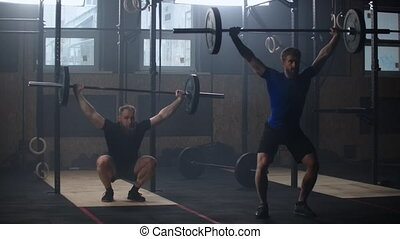 Two athletic male, athletes, doing exercises with the barbell. Slow motion. Two strong men doing weightlifting with barbell at the gym simultaniously