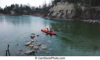 two athletic man floats on a red boat in river - two...