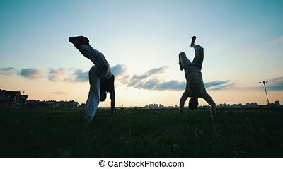 Two athletic men perform somersaults while dancing capoeira on the grass at the summer sunset