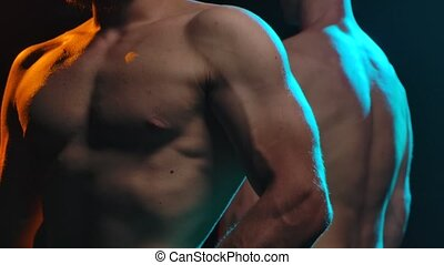 Two athletic naked chested men show off muscles and a strong muscled body. Picture taken in the studio on a black background. Male torso close up. Slow motion