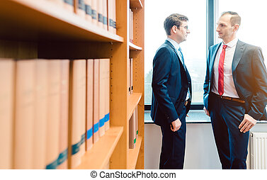 Two attorneys discussing very interesting topics in law firm standing in front of book shelf