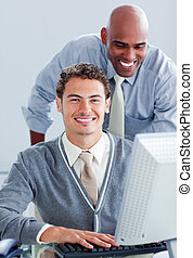 Two attractive businessmen working at a computer
