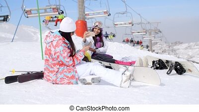 Two attractive female snowboarders sitting in the snow near...