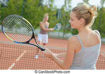 two attractive female tennis players discussion at the court