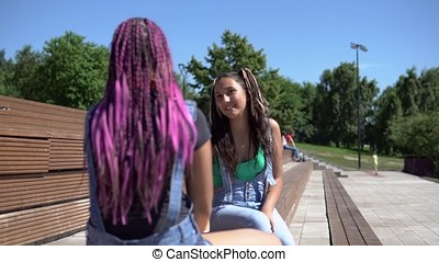 two attractive girlfriends girls communicate with each other having a good mood sitting on a bench in the park. 4K