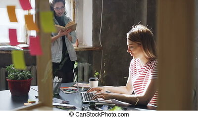 Two attractive girls are working together in modern loft office. Blonde woman is typing on laptop sitting at table while her colleague is reading book standing near window