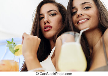 Two attractive girls drinking cocktails