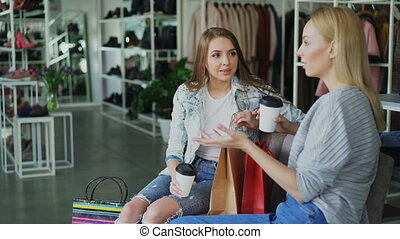 Two attractive girls sitting and talking in women's clothing...