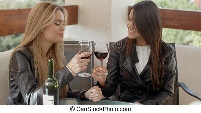 Two attractive girls sitting on balcony with wine