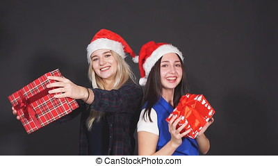Two attractive girls with Christmas gifts in hands laughing and dancing looking at camera.