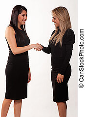 Two attractive hispanic twenties businesswomen talking