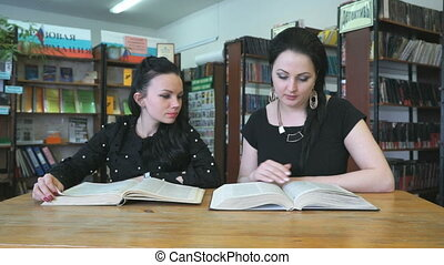 Two attractive ladies reading books at library