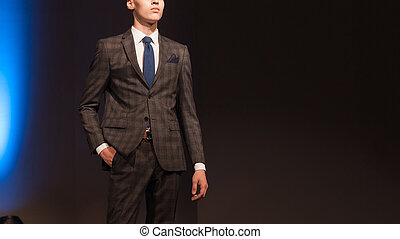 two attractive male models in a stylish suit during a fashion show