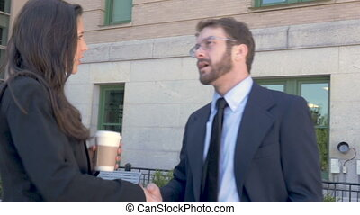 Two attractive millennial businesspeople shaking hands and talking outside
