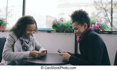 Two attractive mixed race female friends sharing together using smartphone in street cafe outdoors