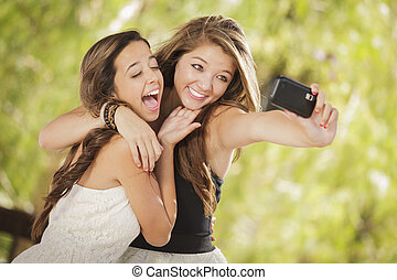 Two Attractive Mixed Race Girlfriends Taking Self Portrait with Their Phone Camera Outdoors.