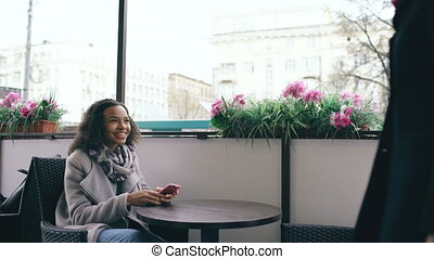 Two attractive mixed race women meet in cafe hugging and sitting together