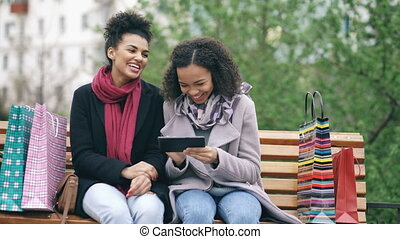 Two attractive mixed race women with shopping bags sitting on bench and using tablet computer for internet surfing. Happy friends have fun after visiting mall sales