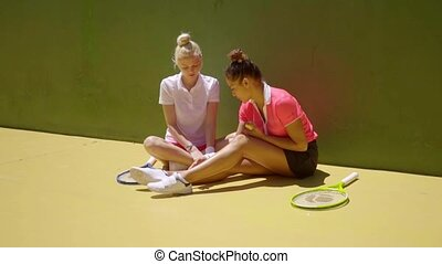Two attractive woman tennis players relaxing