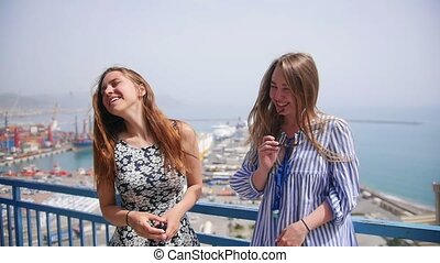 Two attractive women chatting and laughing against the docks - Mid shot