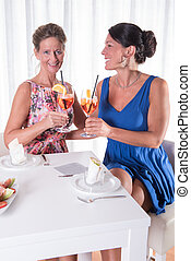 two attractive women having a drink together