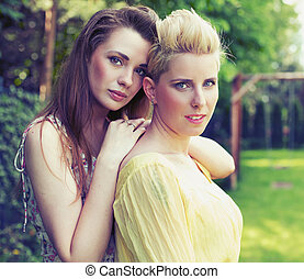Two attractive women posing in the garden