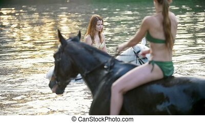 Two attractive women ride on the horses in the river at...
