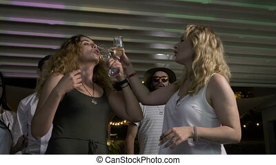 Two attractive women toasting and drinking champagne and...