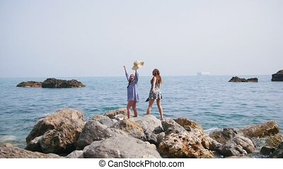 Two attractive women walk along the stony shore in Sorrento...