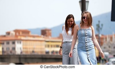 Two attractive women walk straight by touching the pillar. Mid shot