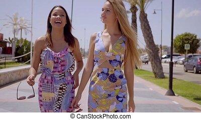 Two attractive women walking along a promenade
