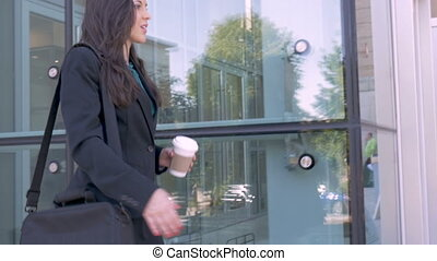 Two attractive young business people shaking hands outside an office building