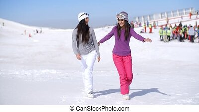 Two attractive young woman walking in fresh snow