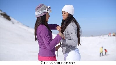Two attractive young women chatting in the snow