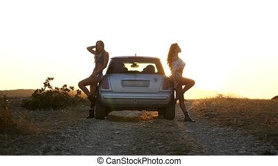 two attractive young women stand leaning on a car in the rays and glare of sunset in the mountains