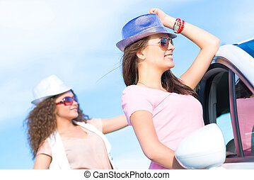Two attractive young women wearing sunglasses