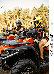 Two atv riders before the trip in summer forest