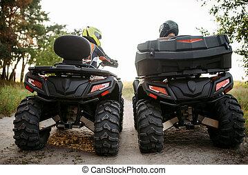 Two atv riders in helmets, back view, quad bike