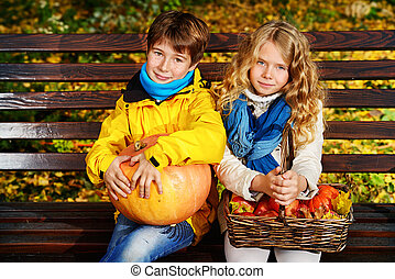 two autumn kids - Happy romantic boy and girl sitting on a ...