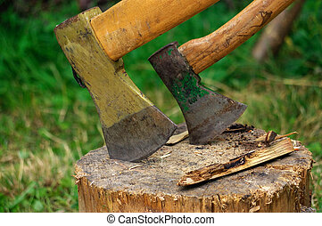 two ax in stump with wood crest on a background of green grass and firewood
