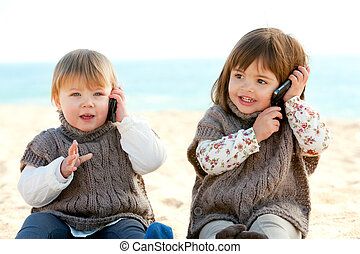 two babie girls talking on mobile phones.