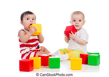 two babies girls playing together with color toys