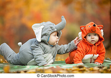 Two baby boys dressed in animal costumes in park - Two baby ...